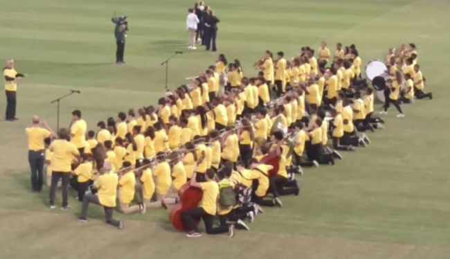 OUSD Honor Band members kneeling at Oakland Coliseum