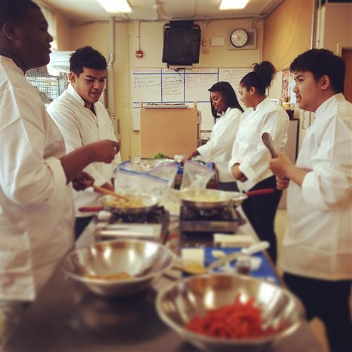 Students gather ingredients before they begin preparing meals.