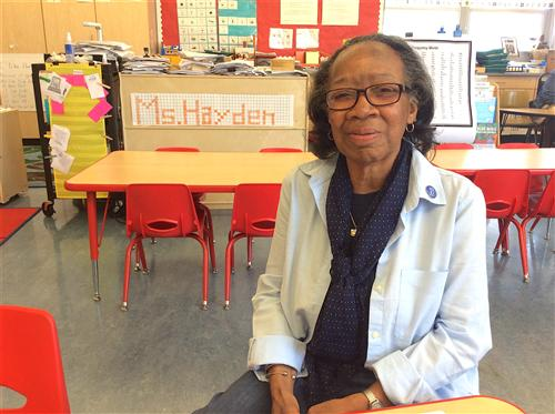 Ms. Hayden sitting in her classroom
