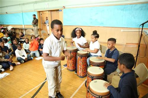 Sankofa Students Play Drums in the Auditorium.