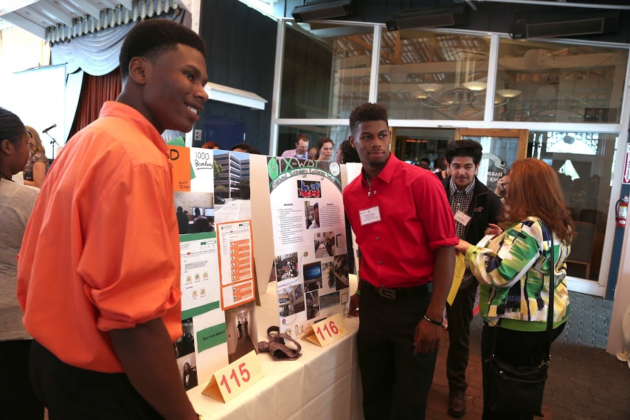 Two African American males present their internship experience to on-lookers.
