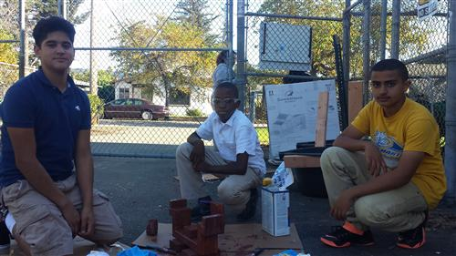 8th grader David Anguiano-Muniz with 7th graders David Ogbe, Ahmed Alomari sit by their project.