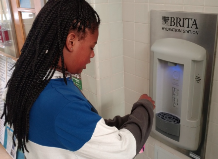 Student filling water bottle at hydration station