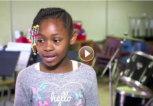 Video still of little girl talking about music program