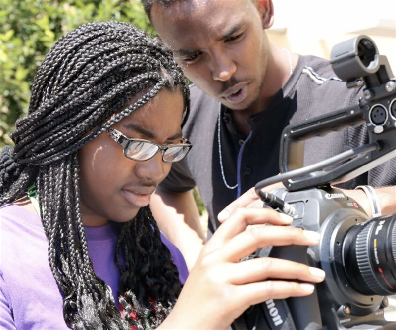 Two students looking through camera
