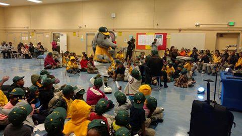The A's mascot visits with students during the assembly.
