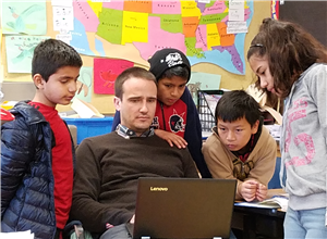 Mr Wallace and students view laptop computer