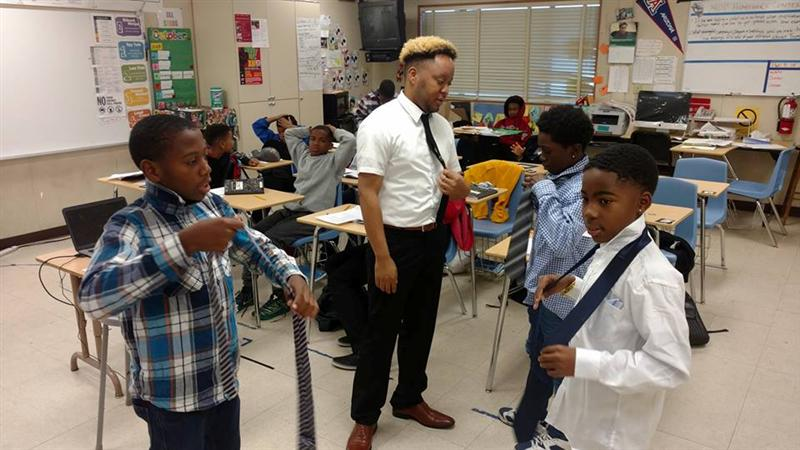 Montera students practice tying a tie.
